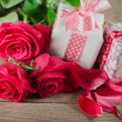 Day. Red roses and holiday gift on a wooden table — Stock Photo #71268279