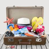 Summer. Retro suitcase with full of clothes,books and passport on blue background — Stock Photo