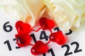 Calendar. Red roses lay on the calendar with the date of February 14 Valentines day — Stock Photo