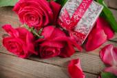 Day. Red roses and holiday gift on a wooden table — Stock Photo