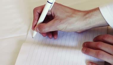 Man writes a pen in a notebook. The phrase I love you. — Vídeo de Stock