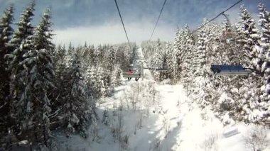 Kayakçı kayak teleferiği üzerinde yükselir. Panorama ve dağlar, ağaçlar karla kaplı manzara çevresinde. Teleferik göster. — Stok video