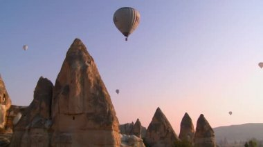 Hot air balloons fly over geological formations — Stock Video