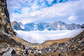 Climbers move in the mountains above the clouds — Stock Photo