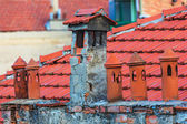 Architecture details of the house with old chimneys and tile roo — Stock Photo