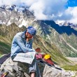 Hiker in the mountains watching the map on at rest — Stock Photo #78033982