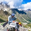 Hiker in the mountains watching the map — Stock Photo #78033984
