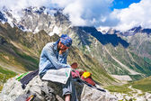 Hiker in the mountains watching the map on at rest — Stock Photo