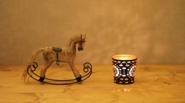 Christmas decoration - wooden toy rocking-horse and candle in candlestick on wooden table against concrete wall — Stock Video