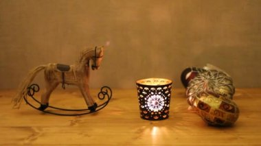 Christmas decoration - wooden toy rocking-horse and candle in candlestick on wooden table against concrete wall — Wideo stockowe