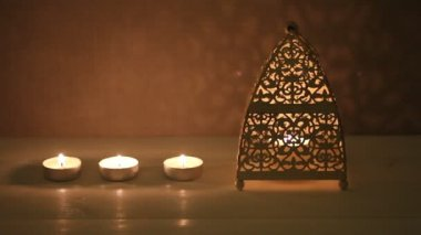 Blazing candles  and candle in candlestick on white wooden table against concrete wall — Vídeo de Stock