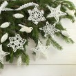 Christmas decoration - white cotton crocheted stars, snowflakes, whitebirds and silver cones on green spruce branches on white wooden background — Stock Photo #77909548