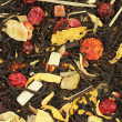Black tea with dried bits of orange, mango, papaya, raspberry, red currant and dried leaves of sunflower, lemongrass, and dried orange flowers — Foto Stock #82454394