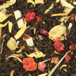 Black tea with dried bits of orange, mango, papaya, raspberry, red currant and dried leaves of sunflower, lemongrass, and dried orange flowers — Foto Stock #82454396