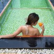 Asian girl drinking glass of orange juice in the pool — Stock Photo #69636805