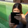 Asian woman holding tablet in the swimming pool — Stock Photo #69636989