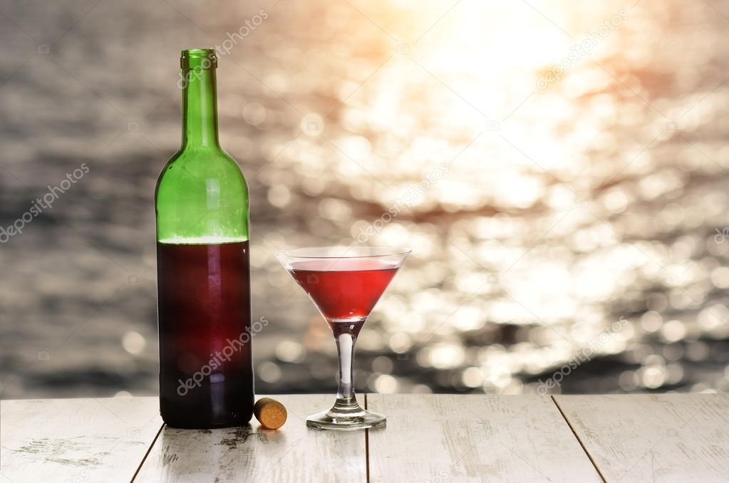 Bouteille et verre de vin rouge sur la table de lin contre la mer ou l 39 oc an sur le coucher de - La bouteille sur la table ...