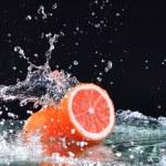 Macro water splash on grapefruit. Water drops with juicy grapefruit — Stock Photo #67334361
