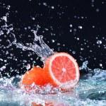 Macro water splash on grapefruit. Water drops with juicy grapefruit — Stock Photo #69548013