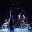Bottle and glass with red wine, water splash, wine on table on dark black background, big splash around Glass and bottle of red wine splash on black — Stock Photo #69548409