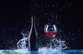 Bottle and glass with red wine, water splash, wine on table on dark black background, big splash around Glass and bottle of red wine splash on black — Fotografia Stock