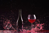 Bottle and glass with red wine, red wine splash, wine pouring on table on dark black background, big splash around Glass and bottle of red wine splash on black — Fotografia Stock