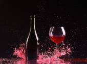 Bottle and glass with red wine, red wine splash, wine pouring on table on dark black background, big splash around Glass and bottle of red wine splash on black — Stock Photo