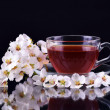 Cup of black tea with cherry branch flowers on dark background — Stock Photo #69550457