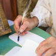 An ancient writer holding a pen made of feather — Stock Photo #66020035