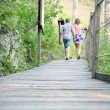Low perspective of loving couple walking on a wooden bridge surrounded by the natural park of the Tuscan Apuan Alps — Stock Photo #73420079