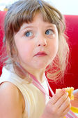 Beautiful blond little dizzy concerned that called and reprimanded while chewing a piece of cake at a birthday party — Stock Photo