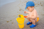 Child two year old in a swimsuit plays to fill a bucket of gravel yellow on the shore of a beach in Versilia (Tuscany) — Stock Photo