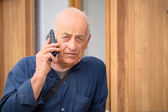 Retired farmer is talking on the phone and it saddens concerned on receipt of bad news — Stock Photo