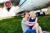 Coppie eleganti che stanno vicino a un aereo all'aeroporto. luna di miele — Foto Stock