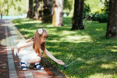 Happy little girl playing with a spray of water in the park — Stock Photo