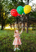Baby girl 2-3 year old holding balloons outdoors. Birthday party — Stock Photo