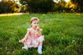 Little girl sitting on the grass. — Stock Photo