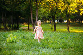 Happy cute little girl running on the grass in the park. Happine — Stock Photo
