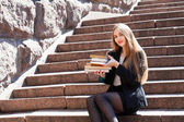 Beautiful girl student is sitting on stairs with stack of books — Stock Photo