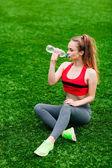 Bella donna sorridente rilassa sull'erba nel parco durante — Foto Stock