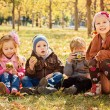 Four happy children playing in autumn park with fruits — Stock Photo #68360851