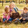 Four happy children playing in autumn park with fruits — Stock Photo #68360871