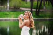 Young beautiful bride in a white dress with a bouquet standing n — Stock fotografie