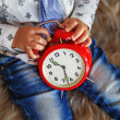 A little boy holding a big red clock waiting for miracles — Stock Photo #74524885