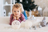 Little girl waiting for a miracle in Christmas decorations — Stock Photo
