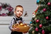Маленький мальчик украшает елку в интерьере с Chris — Стоковое фото