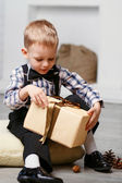 Little boy opening a gift in Christmas decorations waiting for a — Stock Photo