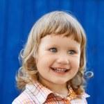 Portrait of happy joyful beautiful little girl against the blue — Stock Photo #84954142