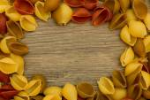 Shell pasta on wooden table top view frame — Stockfoto