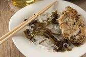 Glass noodles with laminaria and chiken with herbs — Stock Photo